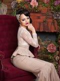 Bella giovane sposa che si siede in una sedia Fotografia Stock