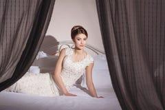 Bella giovane sposa con l'acconciatura di immaginazione e di trucco in vestito operato che si siede sul letto Immagine Stock