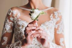 Bella giovane sposa esile che tiene un boutonniere immagine stock