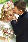 Bella giovane sposa felice che bacia sposo bello nella parità soleggiata Fotografie Stock