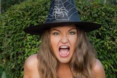 Bella giovane strega nei grida black hat alla macchina fotografica Fotografie Stock
