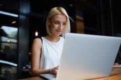 Bella giovane studentessa bionda che per mezzo del computer portatile portatile mentre lavoro al coursework, Fotografia Stock