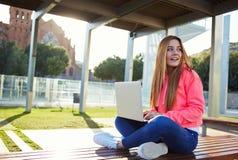 Bella giovane studentessa che si siede su un banco in un computer nella città universitaria Fotografia Stock