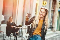 Bella giovane usura di donna alla moda in vestiti di modo e restare davanti al caffè e tenere tazza di caffè nera, Fotografia Stock Libera da Diritti
