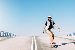 Bella guida della donna del pattinatore sul suo longboard Immagine Stock
