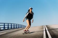 Bella guida della donna del pattinatore sul suo longboard Immagini Stock Libere da Diritti