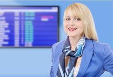 Bella hostess bionda sorridente, pannello d'imbarco su fondo Immagine Stock