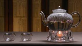 Bella immagine calda del bollitore trasparente della teiera con tè nero verde saporito su una tavola con le candele Bollitore di  immagine stock libera da diritti