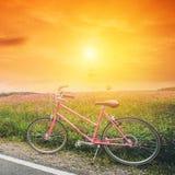 Bella immagine del paesaggio con la bicicletta rosa al tramonto Fotografia Stock