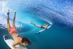 Bella immersione subacquea della ragazza del surfista sotto l'acqua con il bordo di spuma immagine stock libera da diritti