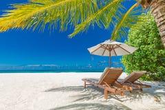 Bella insegna della spiaggia, due sedie del sole ed ombrello sul paesaggio tropicale della spiaggia Concetto di festa e di vacanz fotografia stock