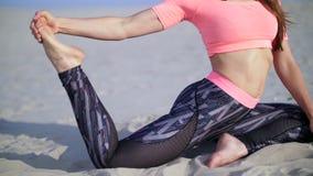 Bella la donna in buona salute e giovane che allunga, yoga di pratica sulla spiaggia, all'alba, fa gli esercizi per equilibrio e stock footage