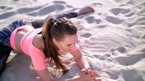 Bella la donna in buona salute e giovane che allunga, yoga di pratica sulla spiaggia, all'alba, fa gli esercizi per equilibrio e video d archivio