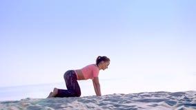 Bella la donna in buona salute e giovane che fa, esegue spinta-UPS, sulla spiaggia, all'alba, fa gli esercizi per equilibrio e video d archivio