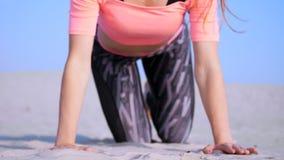 Bella la donna in buona salute e giovane che fa, esegue spinta-UPS, sulla spiaggia, all'alba, fa gli esercizi per equilibrio e archivi video