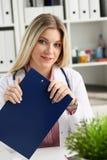 Bella lavagna per appunti femminile sorridente della tenuta di medico Immagine Stock