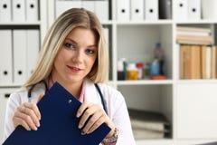 Bella lavagna per appunti femminile sorridente della tenuta di medico Immagine Stock Libera da Diritti