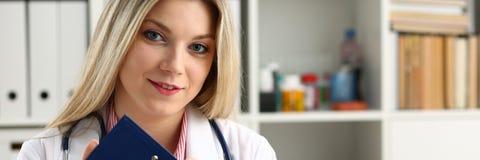 Bella lavagna per appunti femminile sorridente della tenuta di medico Fotografia Stock