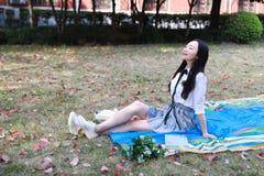 Bella lettura adorabile sveglia felice dello studente di college della High School della ragazza sul prato inglese dell'erba Immagine Stock Libera da Diritti