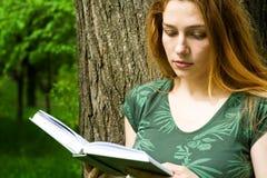 Bella lettura dell'allievo femminile nella città universitaria Immagini Stock