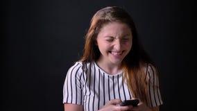 Bella lettura della donna qualche cosa di divertente sul telefono e sulla risata, isolato sul fondo nero dello studio, allegro e  video d archivio