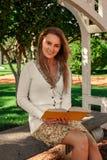 Bella lettura della ragazza dello studente nel parco immagini stock