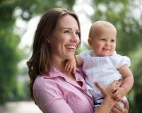 Bella madre che tiene bambino sveglio all'aperto Fotografie Stock Libere da Diritti