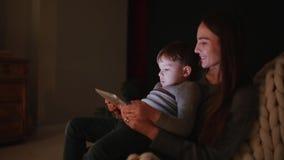 Bella madre della donna che si siede in una sedia la sua casa con il figlio sui suoi fumetti di sorveglianza del rivestimento sul stock footage