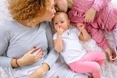 Bella madre e figlia che baciano il bambino che sta selezionando il suo naso immagini stock libere da diritti