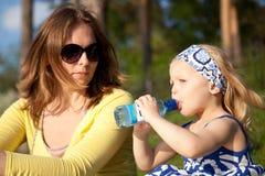 Bella madre e figlia che si siedono sull'erba fotografia stock libera da diritti