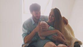 Bella madre felice della famiglia che culla il suo bambino nei picchietti di oscillazione di un padre della sedia sulla testa del Fotografia Stock