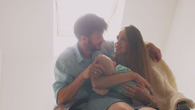 Bella madre felice della famiglia che culla il suo bambino nei picchietti di oscillazione di un padre della sedia sulla testa del Immagini Stock