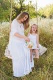 Bella madre incinta con la piccola ragazza bionda in un vestito bianco che si siede su un'oscillazione, ridente, infanzia, rilass Immagine Stock Libera da Diritti