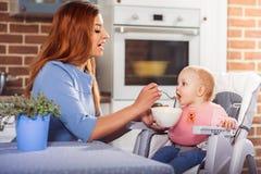 Bella madre in vestito blu che si alimenta con il cucchiaio che la sua strega sveglia della neonata si siede nel seggiolone Immagini Stock