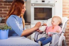 Bella madre in vestito blu che si alimenta con il cucchiaio che la sua strega sveglia della neonata si siede nel seggiolone Immagine Stock