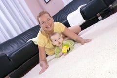 Bella mamma con il suo figlio che gioca felicemente. Immagini Stock