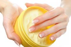 Bella mano con il manicure francese e la crema Fotografia Stock
