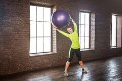 Bella mano della donna alta e palla viola di forma fisica del fermo Fotografie Stock
