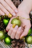 Bella mano femminile con progettazione beige del chiodo Manicure di Natale Fotografia Stock
