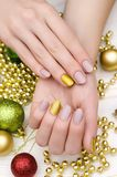 Bella mano femminile con progettazione beige del chiodo Manicure di Natale Fotografie Stock