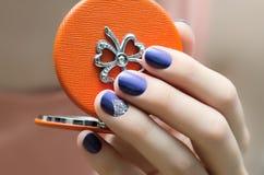 Bella mano femminile con progettazione blu del chiodo Fotografie Stock Libere da Diritti