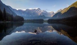 Bella mattina nebbiosa su un lago alpino Immagini Stock