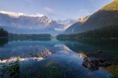 Bella mattina nebbiosa su un lago alpino Fotografie Stock