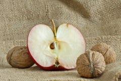 Bella mela rossa con le noci sul sacchetto della tela di canapa Fotografie Stock