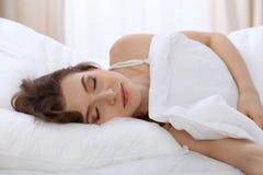 Bella menzogne di sonno della giovane donna a letto e rilassarsi di mattina Gli inizio di un giorno soleggiato è il momento di an Fotografia Stock