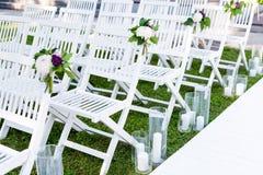 Bella messa a punto di nozze Cerimonia di nozze nel giardino Sedie di legno bianche decorate con i fiori e le candele Immagini Stock
