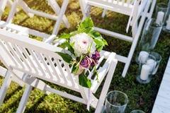Bella messa a punto di nozze Cerimonia di nozze nel giardino Sedie di legno bianche decorate con i fiori e le candele Immagine Stock