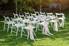 Bella messa a punto di nozze Cerimonia di nozze nel giardino Sedie di legno bianche decorate con i fiori ed i nastri rosa Fotografie Stock Libere da Diritti