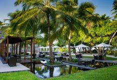 Bella messa a punto tropicale del ristorante di aria aperta con le tavole in acqua circondata dalle palme alle Maldive Immagini Stock Libere da Diritti