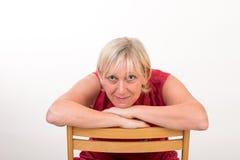 Bella metà di donna invecchiata europea in vestito rosso che si siede o rilassata Fotografia Stock